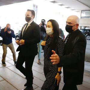 Kaksi tummapukuista miestä kulkee Meng Wangzhoun vierellä. Kaikilla on maskit kasvoillaan. Sivulla kuvaajat ottavat kuvia saapumisesta.