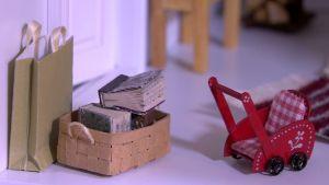 Böcker i korg och barnvagn i miniatyr