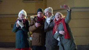 Månssonin perhe laulaa joululauluja ulkona lumisateessa.