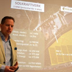 Frank Hoverfelt står vid en bild av en karta.