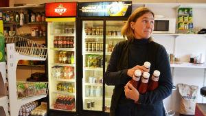 En kvinna står inne i en bybutik. Hon håller i ketchupflaskor.