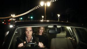 Nick Cave ajaa autoa, Kylie Minougue istuu kyydissä. Kuva dokumenttielokuvasta Nick Cave: 20 000 päivää maan päällä.