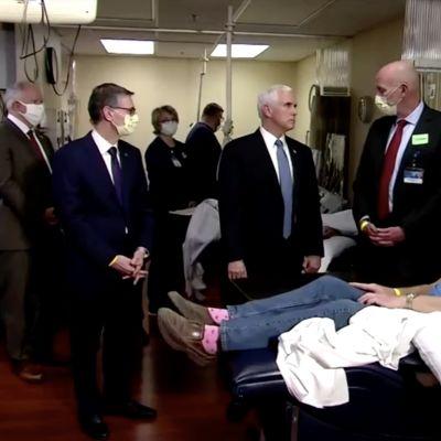 Män i ansiktsmasker står runt USAs vicepresident Mike Pence som inte bär ansiktsmask.