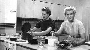 """Tv-ohjelma """"Keittiön puolella"""". Ohjaus Tytti Karttunen, suunnittelu Seija Laakso. Seija Laakso valmistaa pakasteita marjoista. Tumma nainen ja Seija Laakso työskentelevät keittiössä. (1959)"""