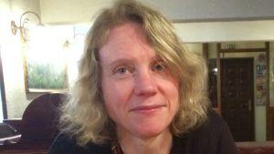 En blond kvinna i svart kofta sitter vid ett bord med händerna knäppta och ser in i kameran.