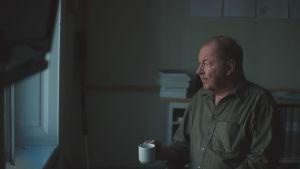 Roy Andersson sitter med en kaffekopp och tittar ut genom ett fönster.