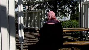 Invandrarkvinna sitter på bänk