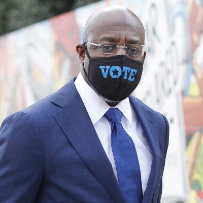 """Collage av två bilder. Till vänster syns en man i kostym och munskydd som poserar framför en målad vägg. Till höger syns en skylt som står på marken med texten """"Vote here"""" samt en bild av USA:s flagga."""