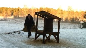 En träställning med en havretunna i och en höbal. Viltbruksföretagare Tomas Landers syns också i bild