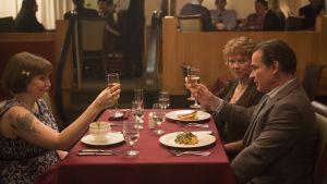 Girls-sarjan Hannah (Lena Dunham) istuu ravintolassa vanhempiensa kanssa.