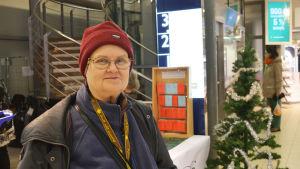 En äldre kvinna står framför en julgran i ett köpcenter.