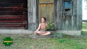 Joogaohjaaja istuu vanhan rakennuksen edessä, kädessä on saunavihta.