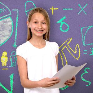Kuvassa on iloisen näköinen tyttö liitutaulun edessä ja hän pitää valkoista paperia kädessään.