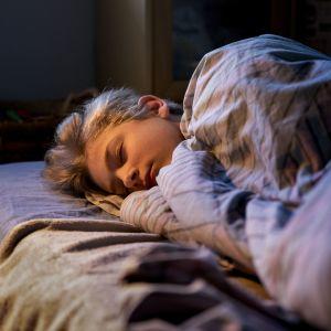 Teini-ikäinen poika nukkuu sängyssään.