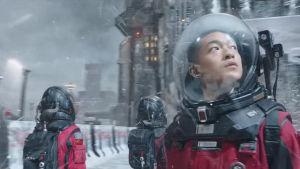 Liu Qi (Chuxiao Qu) står i en rymddräkt och tittar på en vintrig stad.