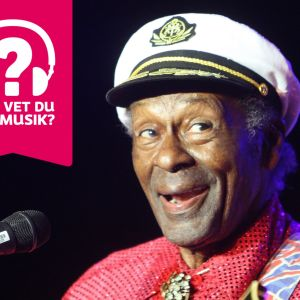 Chuck Berry har en skepparkeps på huvudet och ler med öppen mun.