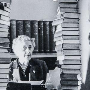 Agatha Christie katsoo kameraan kahden korkean kirjapinon välistä.