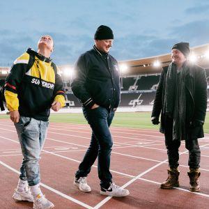 Kolme henkilöä valaistun Olympiastadionin juoksuradalla.