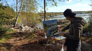 Assol Agaideorova står och målar på en strand i skärgården.