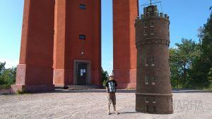 En pojke står bredvid ett vattentorn som är animerat med hjälp av AR-teknik. Alltså förstärkt verklighet.