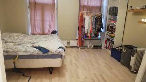 Städat sovrum med kläderna i ställning och bäddad säng