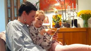 Maarit Feldt-Ranta sitter i en fåtölj med sitt barnbarn i famnen.