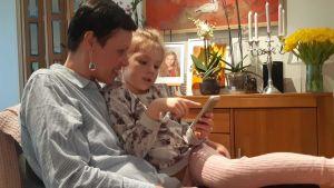 Maarit Feldt-Ranta ja lapsenlapsi tutkivat kännykkää sohvalla.