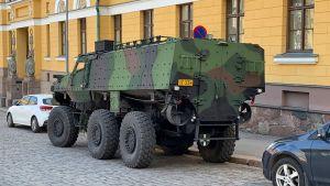 En bild på en misu, ett miitärfordon som står på en gata i en stad.