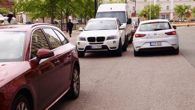 """En bil håller på att fickparkera på """"fel"""" sida vägen."""