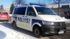Polisbil står parkerad längs vägen, en butik i bakgrunden. Vinter.
