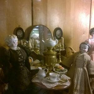 två antika dockor har en tebjudning