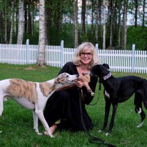 Tutkija Taina Kinnunen kahden vinttikoiransa kanssa pihanurmella. Vasemmalla valkoinen vinttikoira ja oikealla musta.