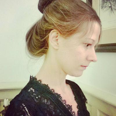 En ung kvinna med uppsatt hår och iklädd svart spetsskjorta.