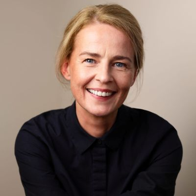 Blond kvinna i svart tröja ler mot kameran.
