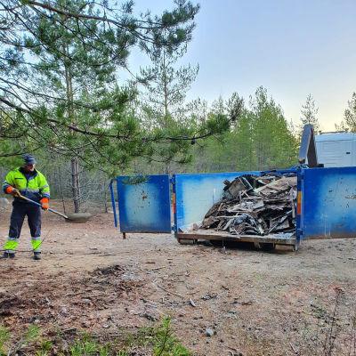 En man städar upp skräp vid en stor container.
