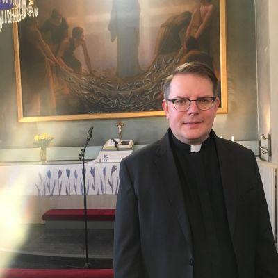 Kirkkoherra seisoo kirkon alttaritaulun edessä.