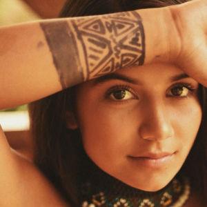 en kvinna tittar intensivt i kameran. hon håller upp ena handen framför panna och har målat symboler på handen. hon har också ett färgglatt pärlhalsband på sig