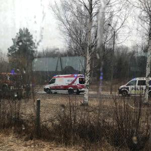 En brandbil, en ambulans och en polisbil på en väg en regnig dag.
