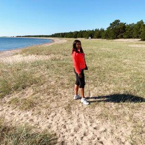 En leende kvinna med  långt mörkt hår och en orange jacka står på en lång sandstrand och ser in i kameran.