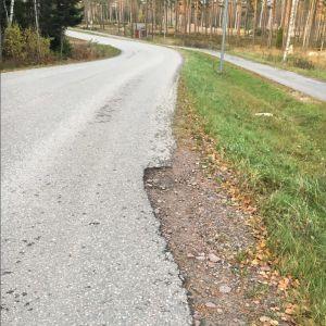 En vägstump med en grop i ena kanten.