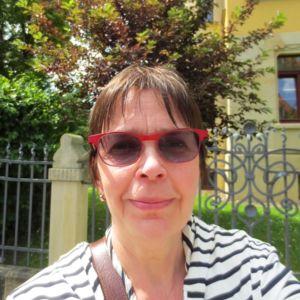 Kirjailija Kati Tervo katsoo hyväntuulisena kameraan taustallaan puu ja kivitalo.