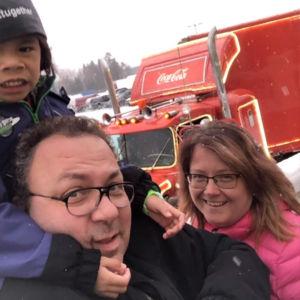 Tre personer framför en Coca Cola långtradare. Två vuxna och ett barn som sitter på en mans axlar.