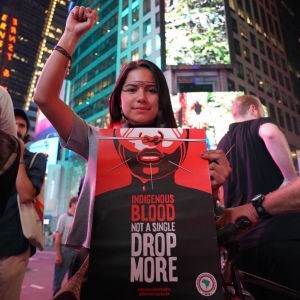 en kvinna håller upp sin hand i en knytkäve och håller framför sig en svartvit skylt som uppmanar folk att sluta döda ursprungsbefolkning. bakom henne finns höghus och hon har också målat symboler i ansiktet