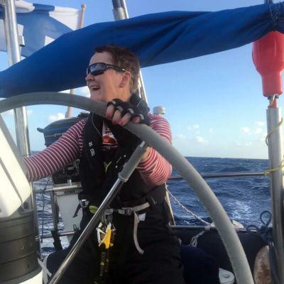 En kvinna står bakom rodret på en segelbåt. I bakgrunden kan man skymta Finlands flagga längst bak i båten.
