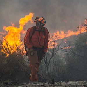 Palomies kulkee etualalla oransseissa haalareissa, kypärä päässään katsoen maahan. Hänen takanaan raivoaa tulipalo. Maisema on savuinen.