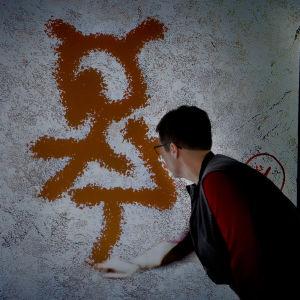 Nainen piirtää kalliomaalaussimulaattorilla.