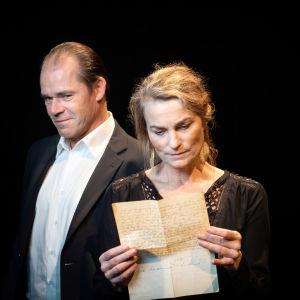 En man i en svart kostym sneglar mot en kvinna som läser ett brev.