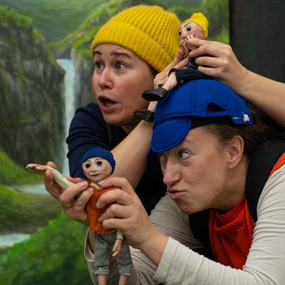 Två skådespelare med handdockor i en teaterpjäs.