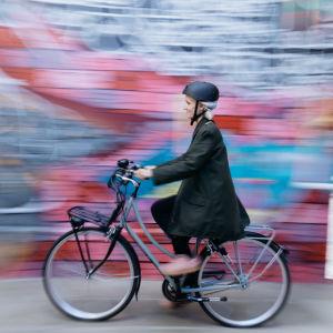 Nainen pyöräilee värikkään graffitin ohi