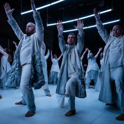 Skådespelare i ljusgrå kappor står med händerna uppsträckta. Ovanför dem i det mörka taket skiner tre lysrör.